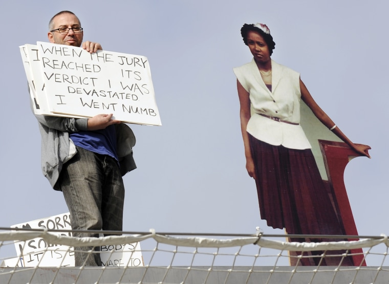 Brian Capaloff, a British activist,holds signs next to a cardboard cut-outof Linda Carty while standing in London's Trafalgar Square on Thursday. The signs show the transcript of an audiotape made by Carty that played at the same time.