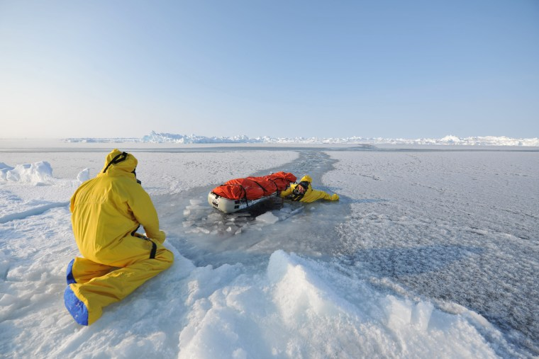 Explorers Pen Hadow and Ann Daniels prepare to swim through thin Arctic ice during their recent 73-day expedition.