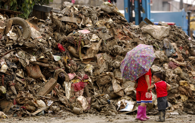 A mother and her child in Marikina, a Manila suburb, on Monday walk past debris left by two earlier storms in the Philippines.