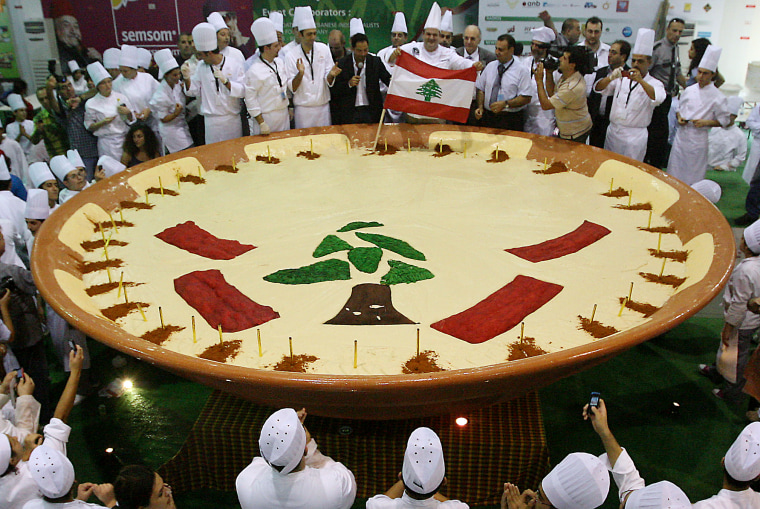 Lebanese chefs celebrate around their hummus creation in Beirut on Saturday. The tree and red bars are taken from the design of Lebanon's flag.