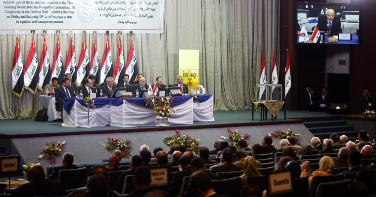 Oil industry officials sit in the audience as Iraqi oil officials go over offers Saturday during the auctionat the oil ministry inBaghdad.