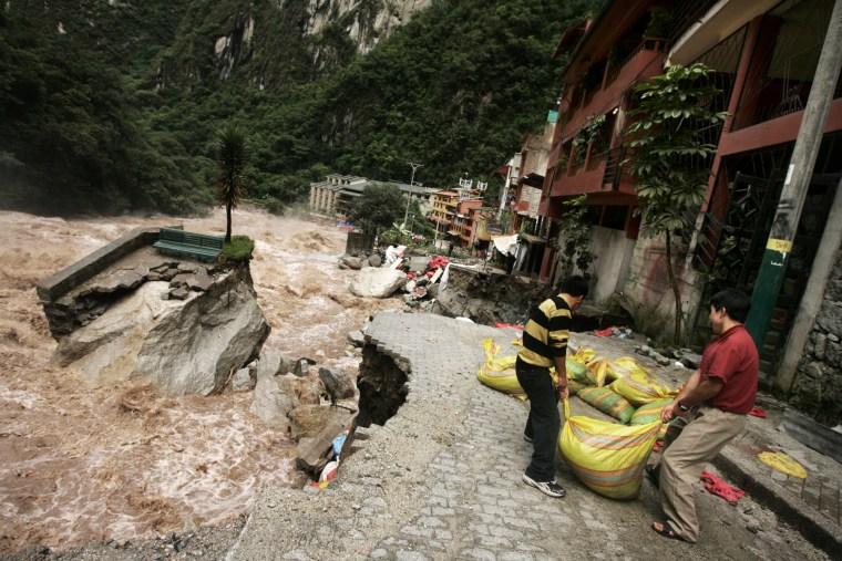 Foreign tourists help move sandbags along theVilcanota Rivernear Machu Picchu on Thursday.