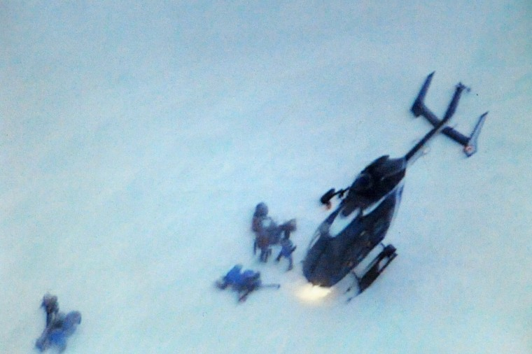 Rescuers land at the site of an avalanche that killed four people Wednesday in the French Alpsat Valmeinier.