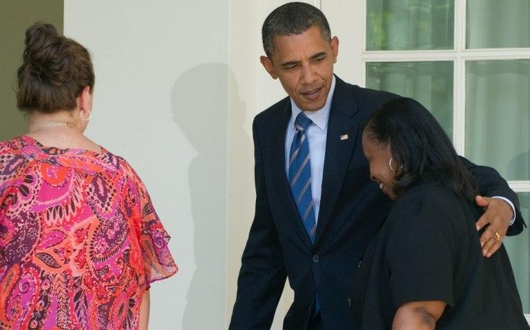 Image: US President Barack Obama puts his arm a