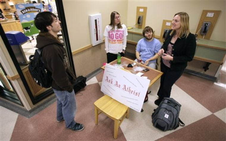 """Iowa State University students chat on Nov. 13 at an """"Ask an Atheist"""" booth on campus."""