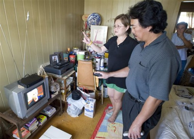 Earl Mostoles, right, helps Arlene Sato set up her digital receiver for her old analog television in Honolulu, Tuesday, Jan. 13, 2009. Hawaii is the first in the nation to make the switch to digital tv from the old analog system. The rest of the states will follow in February.