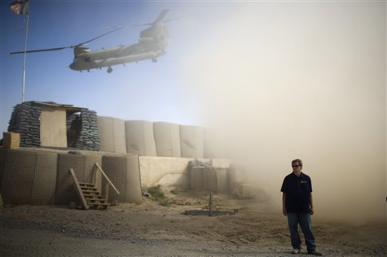 A U.S. contractor looks away from a dust cloud whipped up by a helicopter departing over the gatepost at Combat Outpost Terra Nova in Kandahar, Afghanistan on July 19.
