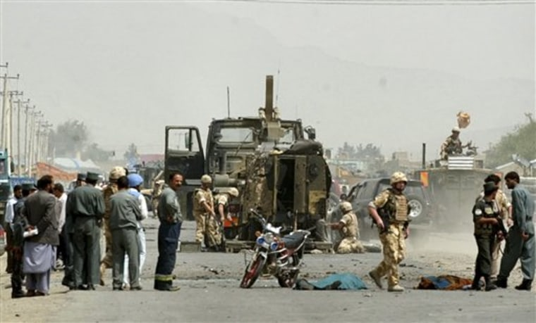 A British soldier from the International Security Assistance Force (ISAF) passes by dead bodies, covered, at the site of a suicide attack in Kabul, Afghanistan.
