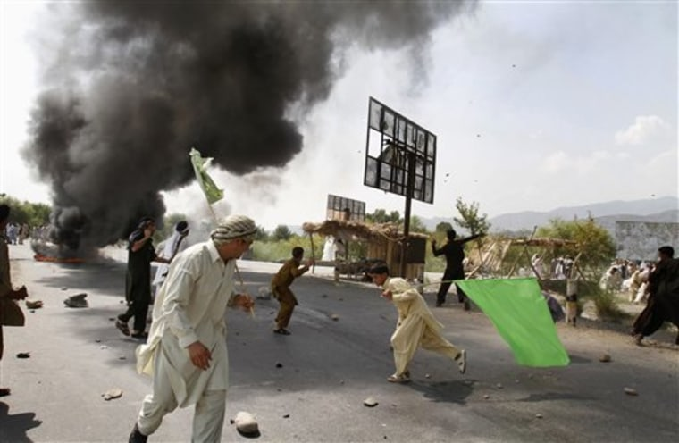 Afghans pelt stones at an election signboard and burn tires blocking a highway, in reaction to a small American church's plan to burn copies of the Quran, at Jalalabad, east of Kabul, Afghanistan, Friday.