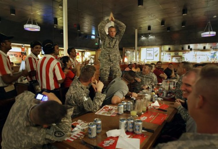 Sgt. Charles Reed, from Steam Boat, Colo., of the 715 Military Intelligence Unit, center, celebrates his 34th birthday with his colleagues and the staff at T.G.I. Fridays restaurant on the boardwalk at Kandahar Air Force Base, Afghanistan on Monday.
