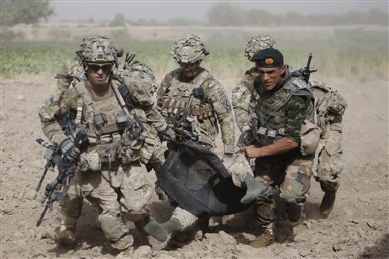 An Afghan National Army soldier along with U.S soldiers carry a wounded U.S soldier following an attack to a medevac helicopter near Kandahar on Saturday.
