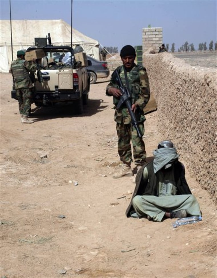An Afghan National Army (ANA) soldier stands guard as a suspected Taliban sits blindfolded and hands tied on the ground in Marjah, city of Helmand province, Feb. 18.