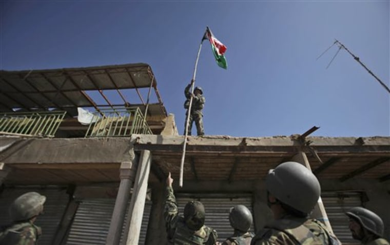 Senior Afghan Army officer instructs a soldier where to hoist an Afghan flag on a building in a market in Marjah, Afghanistan, Wednesday, Feb. 17.
