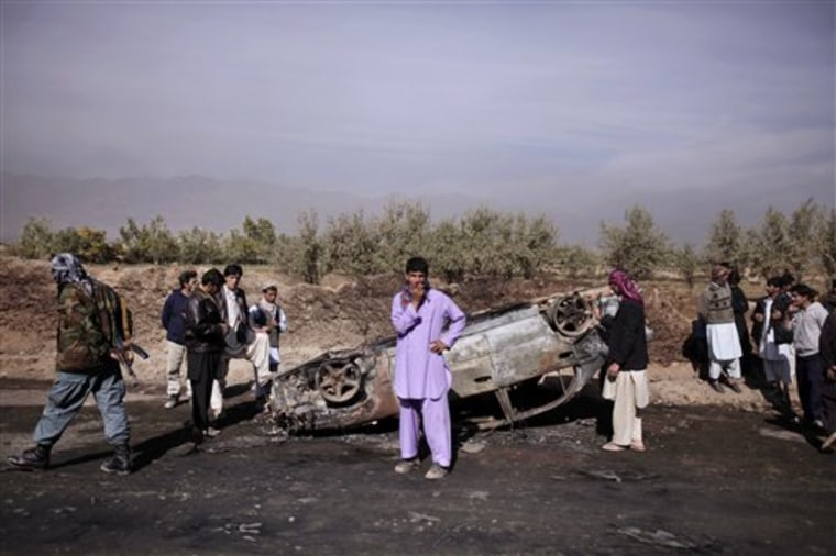 Afghans check a car which was destroyed following an explosion in a fuel tanker in Parwan province, north of Kabul, on Wednesday.