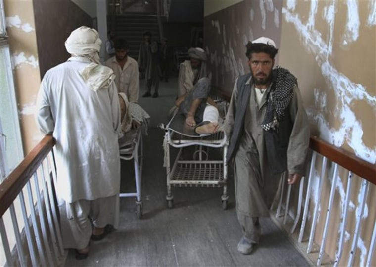 Afghanspush the stretcher with a wounded relative in the hospital in Kandahar south of Kabul, Afghanistan on Tuesday. A roadside bomb killed 10 laborers and wounded 28 on Tuesday as they were being driven to work to clean streams in southern Afghanistan, officials said.