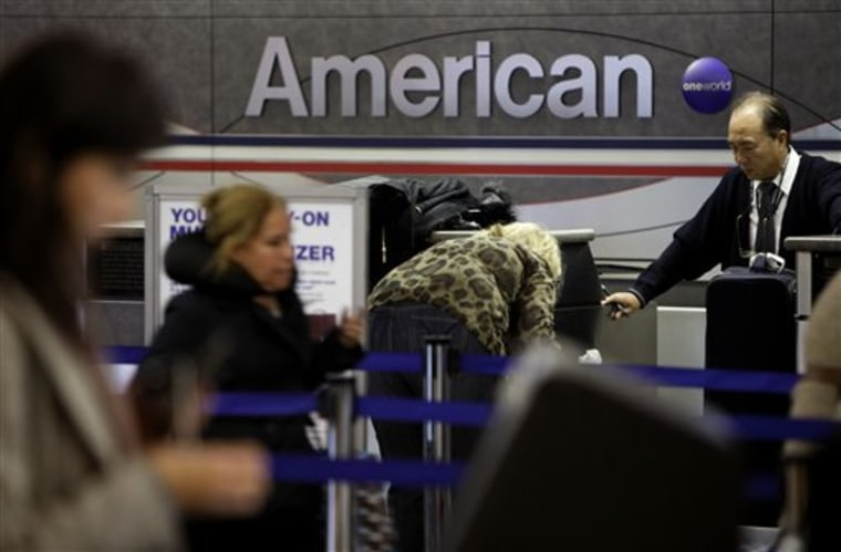 Travelers check in at an American Airlines counter at LaGuardia Airport in New York, Tuesday, Nov. 29, 2011. American Airlines and its parent company are filing for Chapter 11 bankruptcy protection as they seek to cut costs and unload massive debt built up by years of high jet fuel prices and labor struggles.