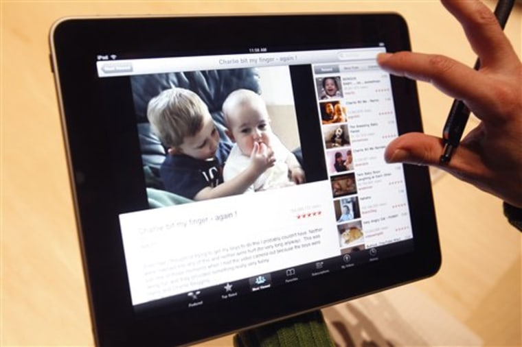 The Apple iPad tablet is examined after its unveiling Jan. 27 in San Francisco. Versions of the device will be available with Wi-Fi only, as well as with a 3G chipfor use on AT&T's wireless network.