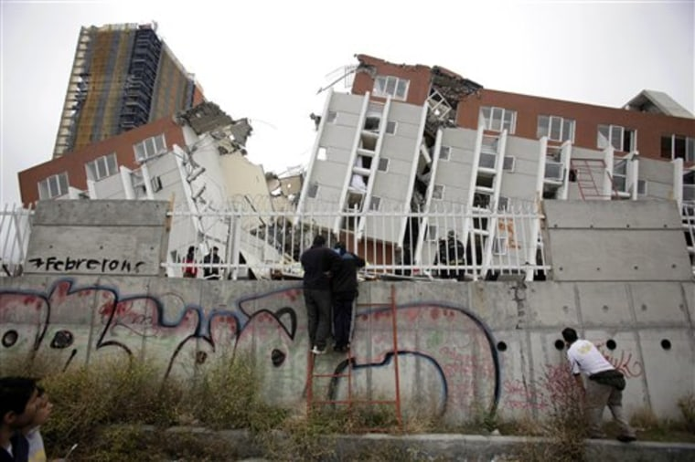 People look at a collapsed building in Concepcion, Chile, on Sunday.