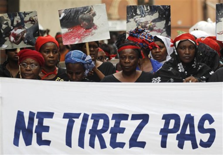 Women carry a banner reading 'Don't shoot' as they participate in a march 'of mourning' for all the victims of post-election violence, in the Treichville neighborhood of Abidjan, Ivory Coast on Tuesday.