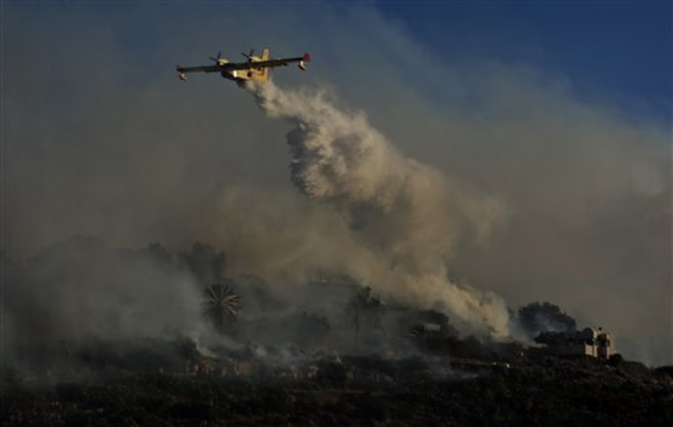 A firefighting plane sprays fire extinguishing material over the fire in Ein Hod, northern Israel, Saturday, Dec. 4, 2010. Residents of a fire-devastated community in northern Israel put out small blazes with hoses and pleaded with firefighters to save their homes, as the worst blaze in the country's history licked through hilly forests on Saturday. (AP Photo/Sebastian Scheiner)