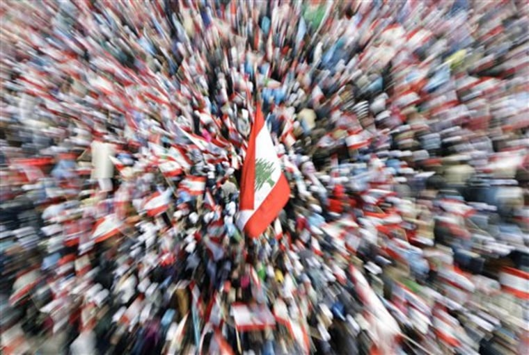 Lebanese people carry national flags as they attend a rally in Beirut's Martyrs' Square, Lebanon, on Sunday. Thousands of flag-waving Lebanese gathered in Beirut's main square Sunday to mark the sixth anniversary of the assassination of former Prime Minister Rafik Hariri, a killing that sparked a cascade of political turmoil in the Middle East.