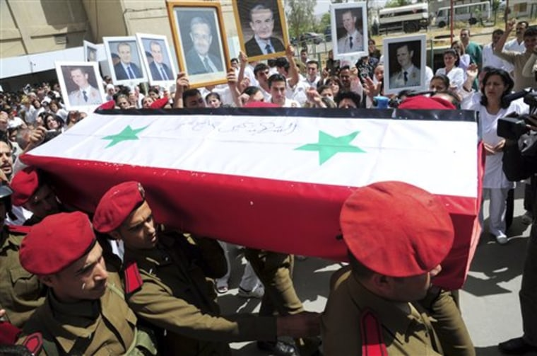 People carry pictures of Syrian President Bashar Assad and his father late President Hafez Assad as Syrian military police carry a coffin preparing to send the bodies of slain soldiers and security force members to their hometowns for burial in Damascus, Syria.