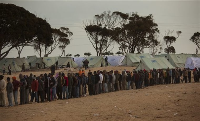 Men, who used to work in Libya but recently fled the unrest, line up as they wait for food in a refugee camp at the Tunisia-Libyan border, in Ras Ajdir, Tunisia, on Tuesday. A Red Crescent official says soldiers loyal to Libyan strongman Moammar Gadhafi are blocking some 30,000 migrant workers from fleeing into Tunisia and forcing many to return to work in the Libyan capital.