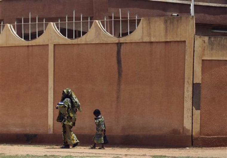 A woman and child walk past the fence surrounding the compound of the Libyan embassy in Niamey, Niger, on Monday. A convoy carrying ousted Libyan leader Moammar Gadhafi's son al-Saadi has crossed into neighboring Niger, a spokesman for Niger's government said on Sunday.