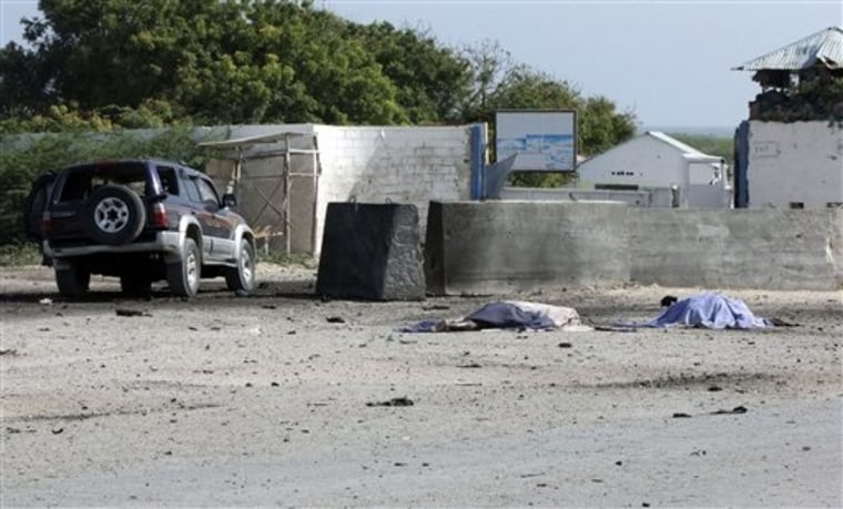 Two bodies lie in front of the Mogadishu airport gate on Thursday. A suicide car bomber and gunmen attacked the front gate to Mogadishu's seaside airport on Thursday, triggering an explosion and gunbattle, officials said. Several people were killed, including security forces.