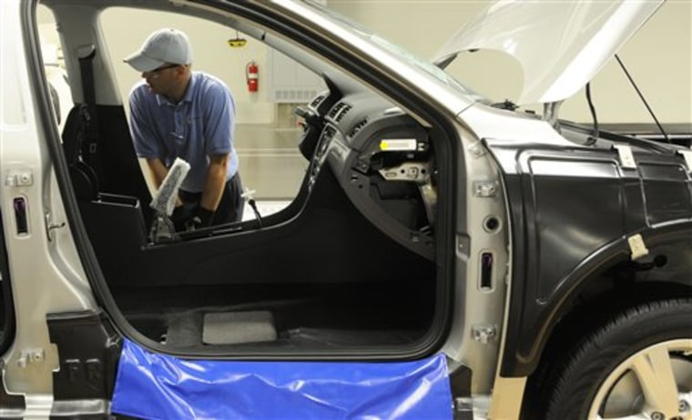Ben Edwards makes adjustments to the door frame of a Passat in Chattanooga, Tennessee. Edwards is a new employee at the Volkswagen plant which opened on May 24.