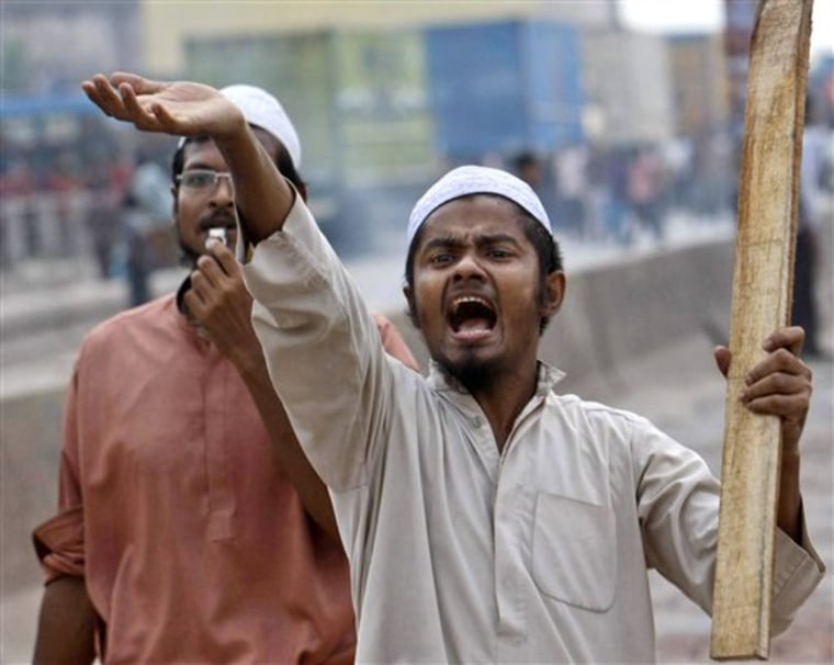 "An Islamic activist armed with a stick shouts as he enforces a 30-hour nationwide strike at Kachpur, outskirts of Dhaka, Bangladesh, on Sunday. Riot police in Bangladesh fired tear gas shells to disperse thousands of Islamist activists trying to enforce an anti-government general strike which has been called by a coalition of 12 Islamic parties to protest removal of a clause from the country's constitution that expressed ""absolute faith and trust in Allah."""