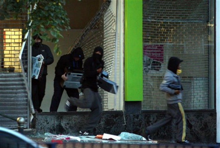 Youths run from an electronics store in Birmingham, England, on Aug. 9. As Britain comes to grips with the causes of the past week's descent into anarchy, Prime Minister David Cameron has identified the growth of gangs as a key factor and is recruiting high-profile American anti-gang experts to help bring them to heel.