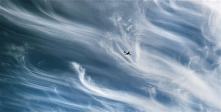 A plane flies over central London in a sky covered by cirrus clouds as the Icelandic ash cloud moved away from British skies. Volcano experts in Iceland said the eruption appeared to be tapering off.