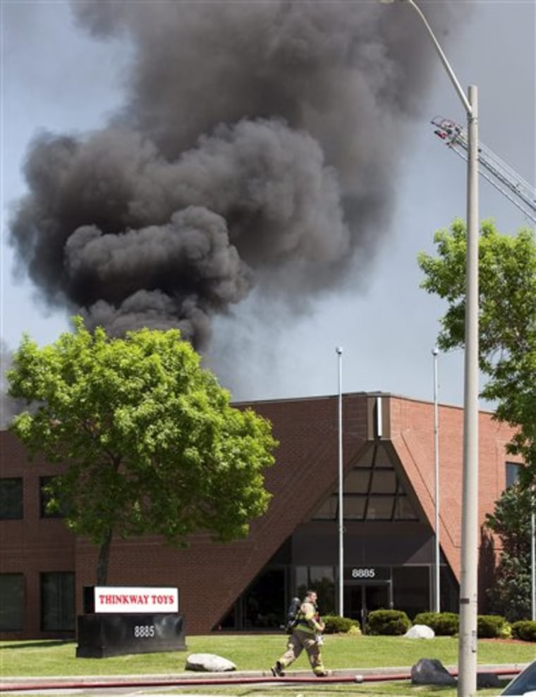 A firefighter runs in front of the Thinkway Toys Division building in Markham, Ontario, after an aircraft crashed into the roof of the building on Tuesday.