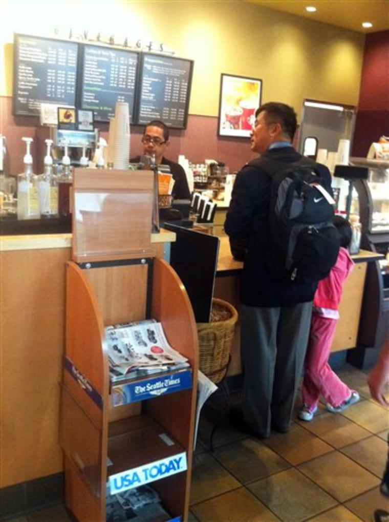 In this photo provided by ZhaoHui Tang, former Washington Gov. Gary Locke, who is the first Chinese-American ambassador to China, orders coffee Friday at Seattle Tacoma International Airport.