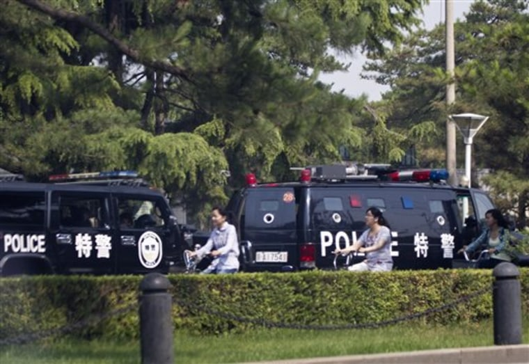 Chinese women bike past police vehicles parked near the main entrance of the Diaoyutai State Guesthouse where North Korean leader Kim Jong-il is believed to have stayed while in Beijing.