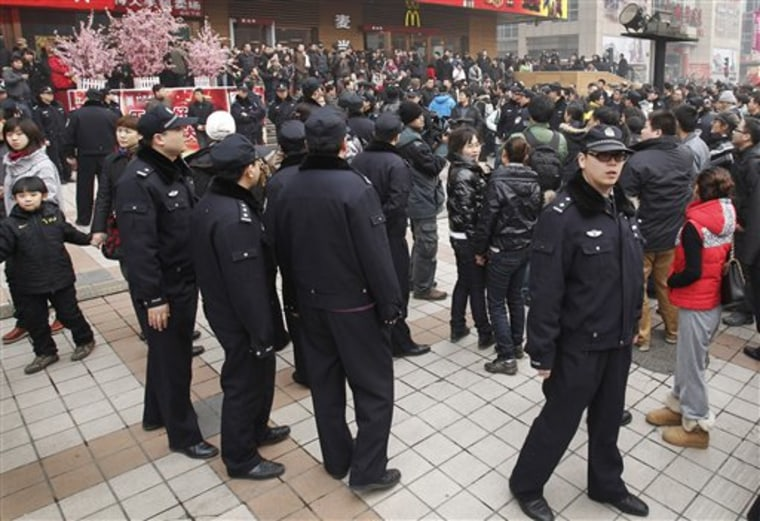 "In this photo taken on Sunday, police officers watch people gathering in front of a McDonald's restaurant that was a planned protest site for ""Jasmine Revolution"" in Beijing."