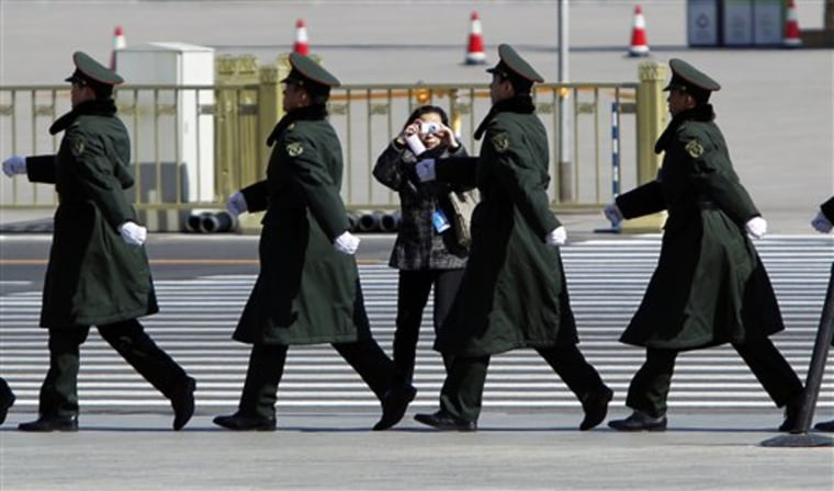 A Chinese woman takes a photo of a group of security personnel outside Beijing's Great Hall of the People, China, where the Chinese People's Political Consultative Conference is in session on Thursday. Chinese police have warned foreign reporters to stay away from spots designated for weekly protests, threatening them with loss of their work permits and other punishments if they don't comply, journalists said Thursday.