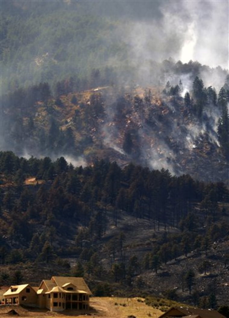 A wildfire burns in Loveland, Colo. on Sept. 13. Firefighters worked Monday to control a wildfire that destroyed at least two homes in the northern Colorado foothills as authorities said the blaze and another one that burned at least 166 homes were sparked by household fires.