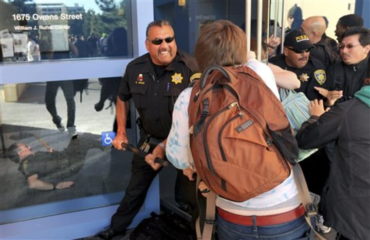 A police officer uses a baton to fend off protesters attempting to enter a University of California regents meeting on Wednesday in San Francisco.