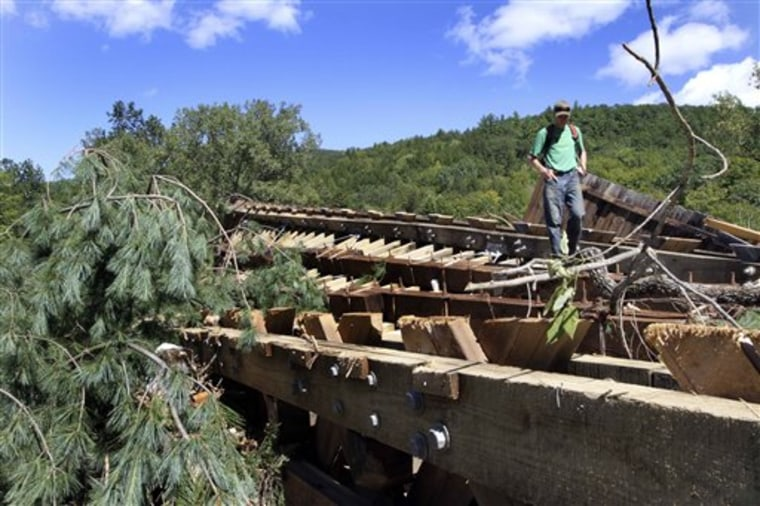 ADVANCE FOR USE SUNDAY, OCT. 9, 2011 AND THEREAFTER - In this Monday Aug. 29, 2011 photo, Teo Campbell stands on what used to be the bottom of the Bartonsville Covered Bridge over the Williams River in a field along the river in Rockingham, Vt. downstream from its original location after heavy rains from Hurricane Irene tore the bridge out. If you had to choose one symbol that sums up the state's essence, it might well be the covered bridge. Besides being tourist magnets, the bridges embody a reverence for history and the rural landscape, a prized sense of community. But the spans are vulnerable. Until Irene hit on Aug. 28, Vermont still had 101; the storm destroyed two and damaged 13 others. (AP Photo/Jim Cole)