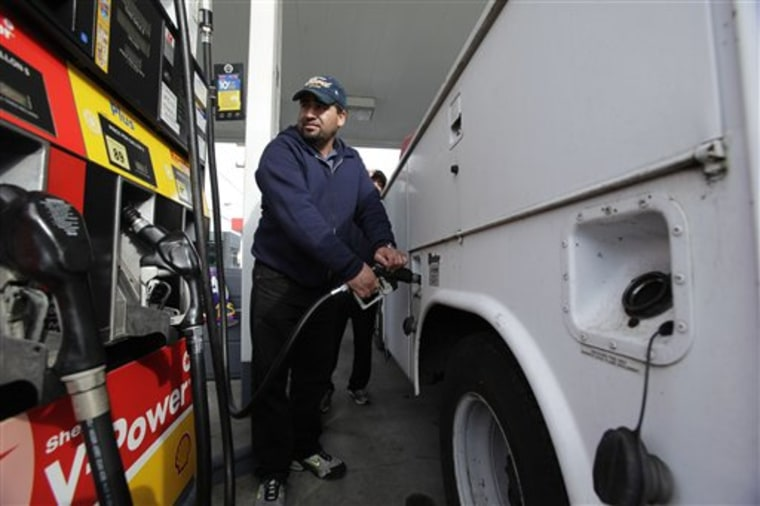 A motorist fills up at a Shell gas station in Seattle. The economy slowed sharply in the first three months of the year as higher gasoline prices cut into consumer spending.