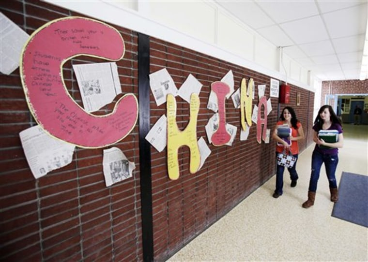Students walk by a display about China at Stearns High School in Millinocket, Maine, on March 10. The public high school recruited students from China to help boost enrollment and revenues. But only six Chinese students will attend high school in fall 2011.