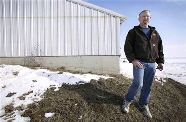 Doug Boyer of Oakville, Iowa, stands near a hog confinement building on his farm that shows a high water mark from the flood of 2008. He's among those critical of FEMA's new flood maps..
