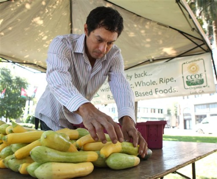 Organic farmer Luis Miranda places summer squash out for sale July 7 at a farmer's market in Sacramento, Calif.