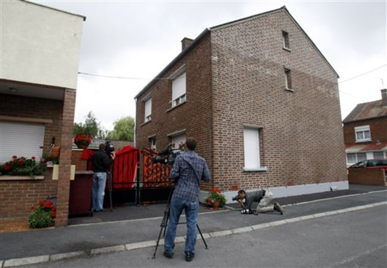 Reporters are seen in front of the house where French police found the corpses of eight newborn babies, in Villers-au-Tertre, northern France on July 29.