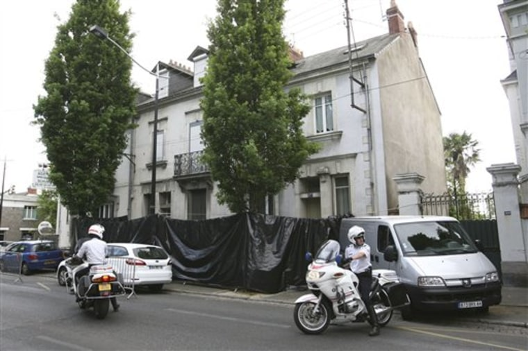 French police motorcyclists are seen in Nantes, western France, outside the house of a French family who have been missing since early April, and where a severed leg was discovered Thursday.