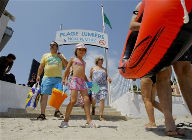 Beachgoers arrive Aug. 2 at La Ciotat beach, where smoking is banned, near Marseille in southern France.