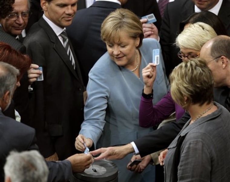 German Chancellor Angela Merkel casts her vote after a debate about the future of nuclear power at the German Federal Parliament, Bundestag, in Berlin, Germany, Thursday, June 30, 2011.