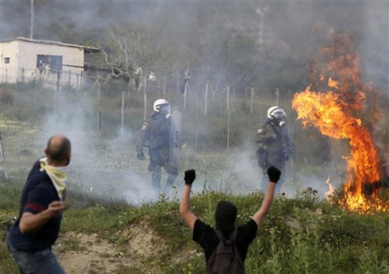 Protesters attack with gas bombs and stone against riot police during clashes in the town of Keratea, about 50 kilometers (31 miles) southeast of Athens, Thursday, April 14, 2011. Greek protesters have used excavators to cut a shoulder-high trench on a busy road near a proposed new landfill, cutting off traffic outside Athens. Youths clashed later Thursday at the site with riot police, who responded with tear gas. (AP Photo/Thanassis Stavrakis)